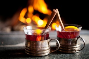Mulled wine with cinnamon sticks in front of a fireplace